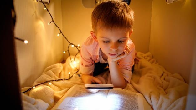 Porträt des kleinen intelligenten jungen, der nachts großes geschichtenbuch liest. kind, das im spielzeugpappehaus spielt konzept der kindererziehung und des lesens in der dunkelkammer.