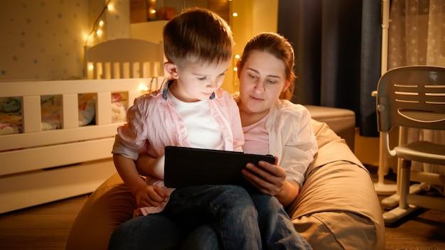 Porträt des kleinen jungen, der auf dem schoß der mütter sitzt und nachts cartoons auf dem tablet-computer ansieht. konzept der kindererziehung und der familie, die nachts zeit zusammen haben.