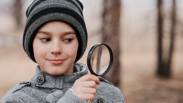Porträt des kleinen jungen, der durch eine lupe mit kopienraum schaut