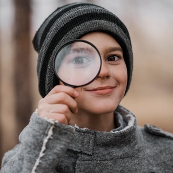 Porträt des kleinen jungen, der durch eine lupe schaut