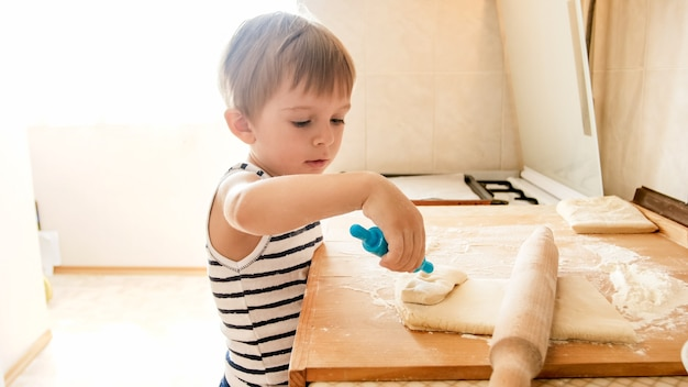 Porträt des kleinen jungen, der teig auf hölzerner küchenarbeitsplatte macht. kinderkuchen oder kekse zum frühstück backen