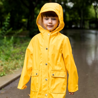 Porträt des kleinen jungen im regenmantel