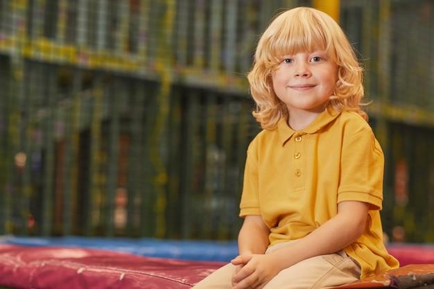 Porträt des kleinen jungen mit blondem haar, das vorne schaut, während auf trampolin im park sitzt