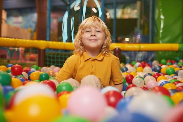 Porträt des kleinen jungen mit dem blonden haar, das vorne lächelt, während im pool mit farbigen kugeln sitzt
