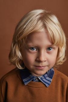 Porträt des kleinen jungen mit langen blonden haaren, die gegen den braunen hintergrund schauen
