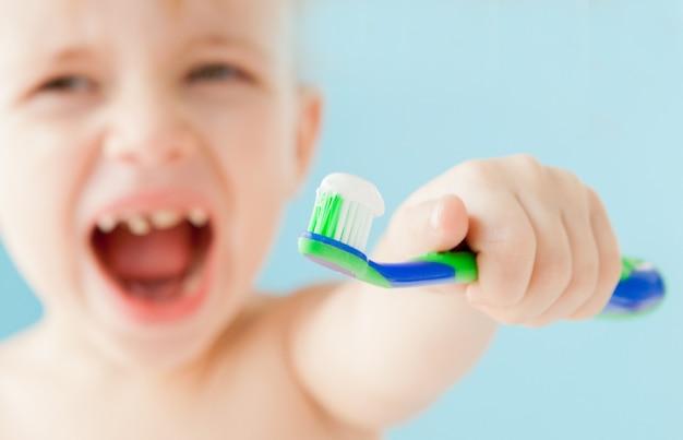 Porträt des kleinen jungen mit zahnbürste auf blauem hintergrund