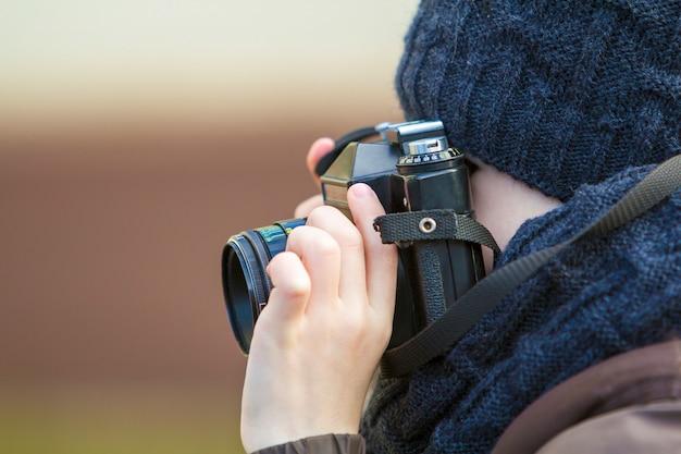 Porträt des kleinen jungenfotografen mit weinlesekamera