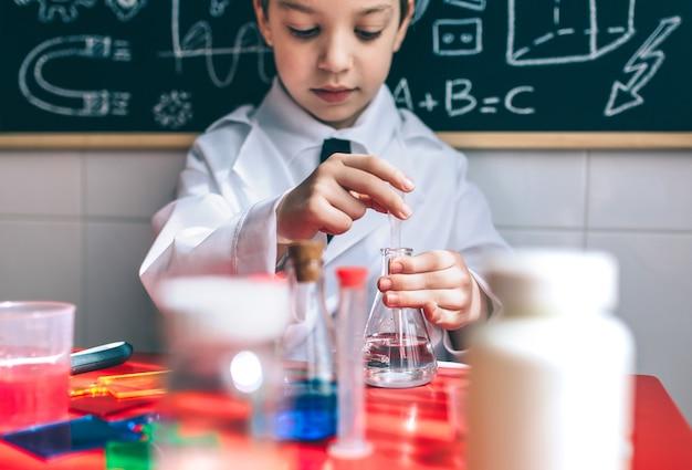 Porträt des kleinen jungenwissenschaftlers, der flüssigkeit aus der flasche gegen die tafel mit zeichnungen extrahiert. selektiver fokus auf kolben.