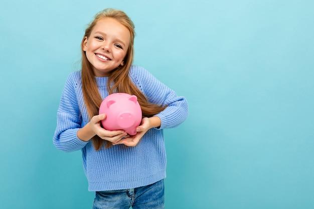 Porträt des kleinen kaukasischen mädchens mit langen haaren hält rosa schwein moneybox lokalisiert auf blauem hintergrund