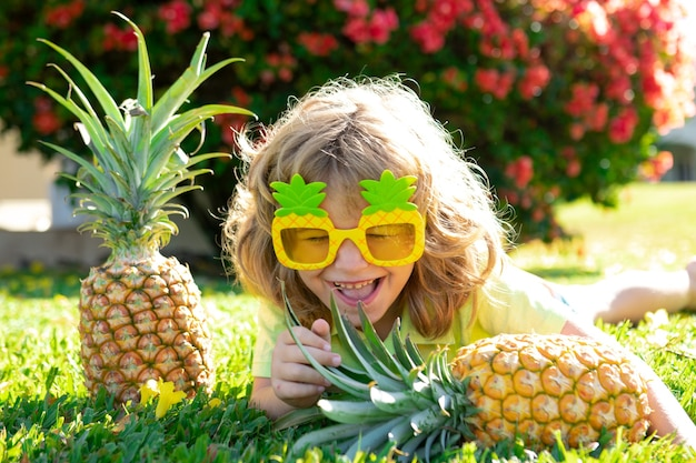 Porträt des kleinen kindes draußen im sommer. lächelnder netter lustiger junge, der eine ananas hält.