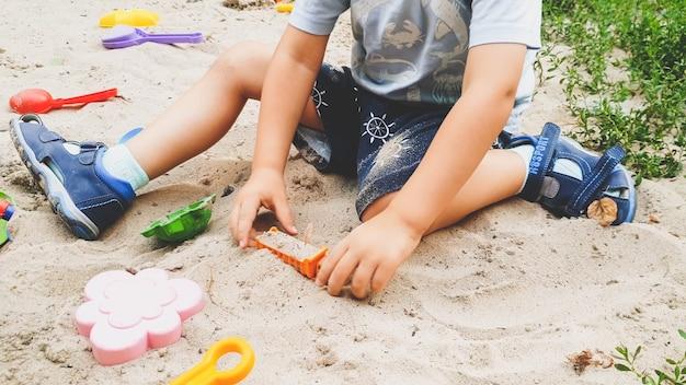 Porträt des kleinen kleinkindjungen, der mit spielzeug und sand auf dem eplayground spielt