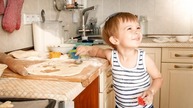 Porträt des kleinen lächelnden jungen, der zu hause auf kithcen kocht