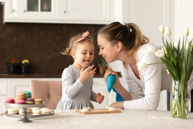 Porträt des kleinen lustigen mädchens und ihrer mutter, die macarrons und kekse in der küche backen. glückliches familien- und muttertagskonzept