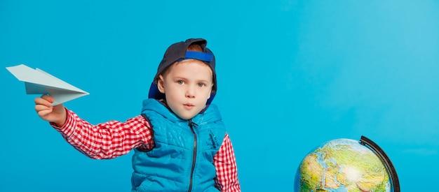Porträt des kleinen lustigen schuljungen mit spielzeugpapierfläche