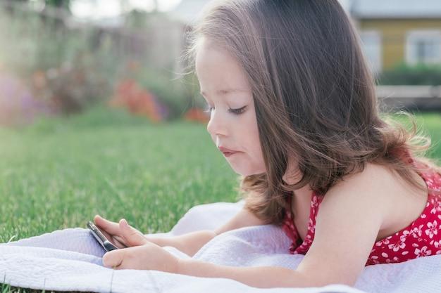 Porträt des kleinen mädchens 3-4 in der roten kleidung, die auf decke auf grünem gras liegt und handy untersucht. kinder mit gadgets