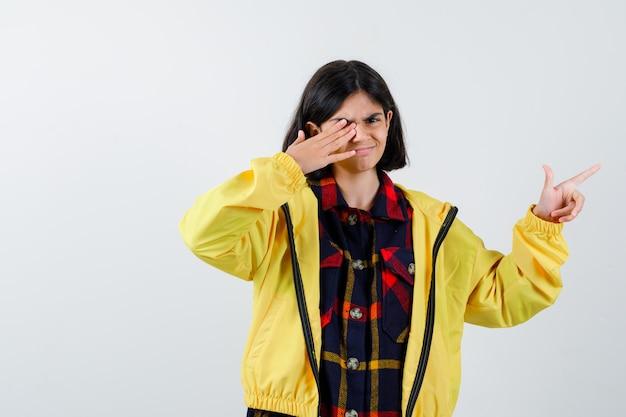 Porträt des kleinen mädchens, das auf die rechte seite im karierten hemd, in der jacke und in der selbstbewussten vorderansicht zeigt