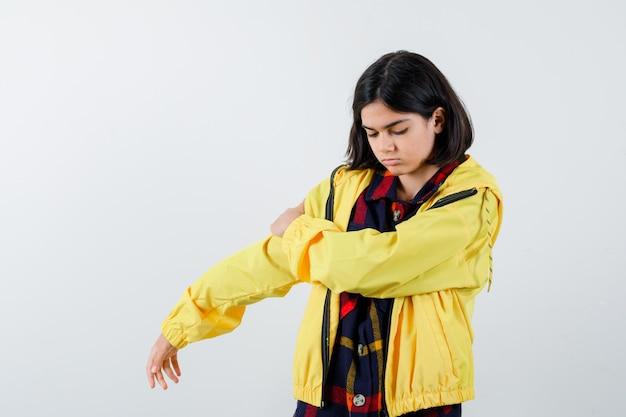 Porträt des kleinen mädchens, das hand auf arm im karierten hemd, in der jacke und in der nachdenklichen vorderansicht hält