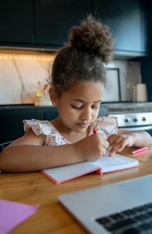 Porträt des kleinen mädchens, das mit laptop zu hause studiert. online schule