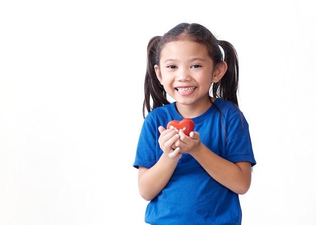 Porträt des kleinen mädchens, das rotes herz auf weißem hintergrund hält. platz für text