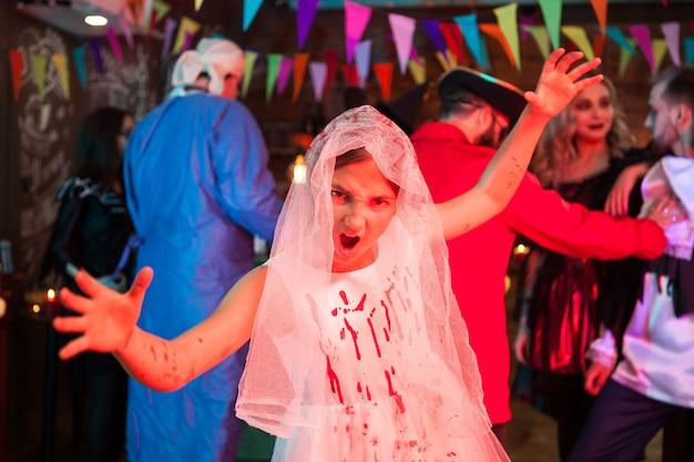 Porträt des kleinen mädchens, das wie eine braut für halloween verkleidet schreit. monster auf einer halloween-party.