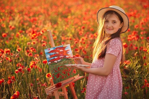 Porträt des kleinen mädchens im feld der roten mohnblumen bei sonnenuntergang und malerei auf der leinwand auf einem zeichenständer