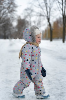 Porträt des kleinen mädchens im warmen overall, der im winterpark geht. vertikaler rahmen.