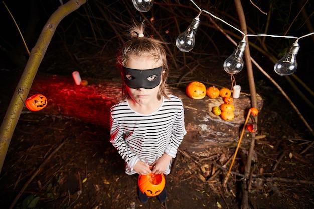 Porträt des kleinen mädchens in der maske mit spielzeugkürbis beim stehen im dunkeln bei der halloween-party