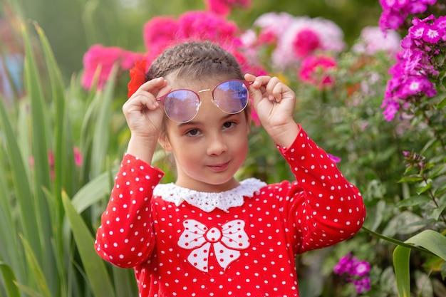 Porträt des kleinen mädchens in einem roten kleid mit polka in gläsern