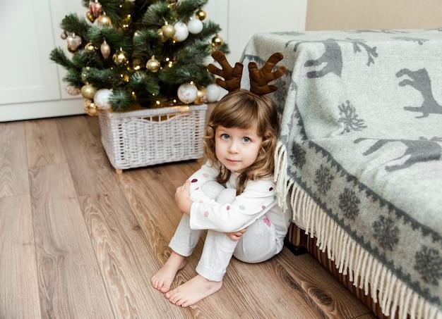 Porträt des kleinen mädchens mit braunem lockigem haar und großen blauen augen