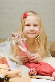 Porträt des kleinen mädchens mit handgemachtem spielzeug nach hause
