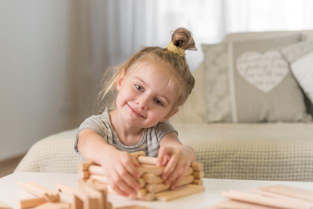 Porträt des kleinen mädchens mit hausmodell.