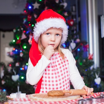 Porträt des kleinen mädchens mit nudelholzbacken-lebkuchenplätzchen für weihnachten