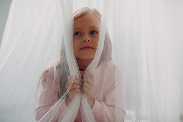 Porträt des kleinen mädchens mit vorhang