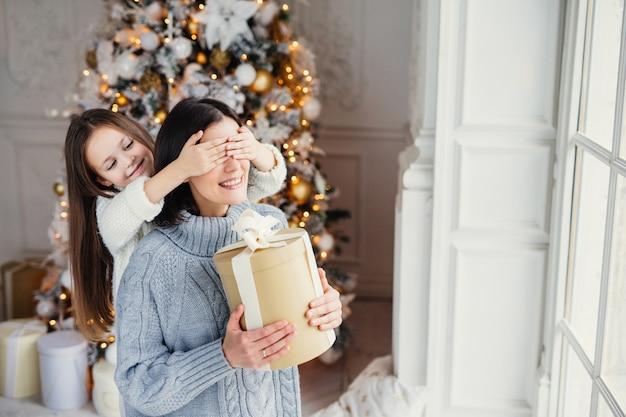 Porträt des kleinen mädchens schließt mutter `s augen, beglückwünscht sie mit neujahr oder weihnachten, steht nahe fenster im wohnzimmer, hat wirkliches wunder und gefühl des feiertags. winter, feier, jahreszeit