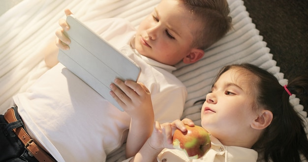Porträt des kleinen mädchens und des jungen, der digitale tablette verwendet