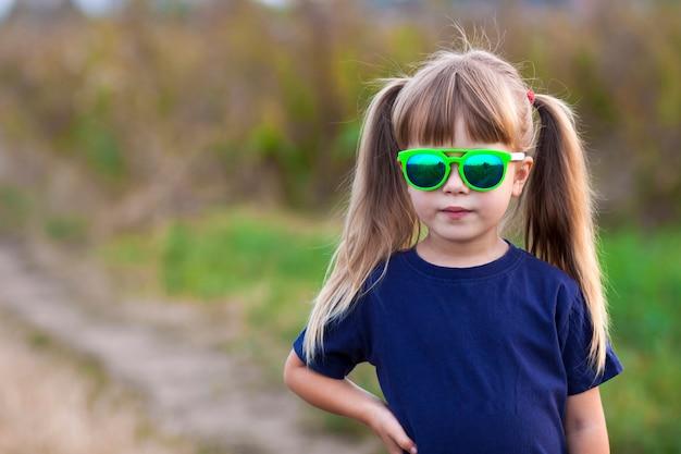 Porträt des kleinen modernen mädchens in der grünen sonnenbrille draußen