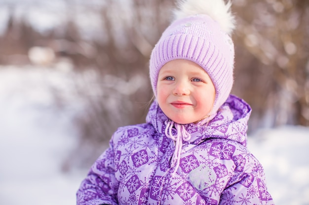Porträt des kleinen netten glücklichen mädchens am sonnigen wintertag des schnees