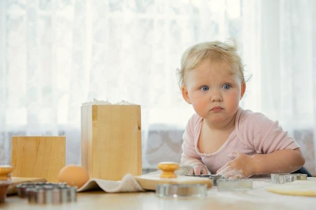 Porträt des kleinen niedlichen lustigen babys befleckt in mehl, das auf küche kocht