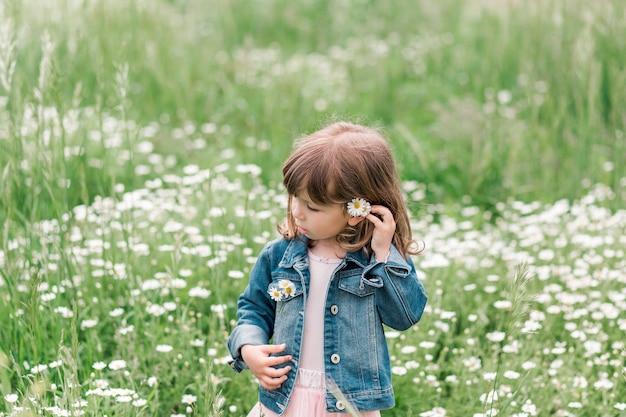 Porträt des kleinen niedlichen mädchens auf dem feld mit gänseblümchen.