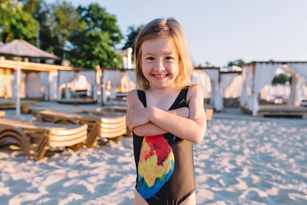 Porträt des kleinen niedlichen mädchens gekleidet im schwarzen badeanzug am strand