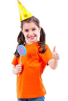 Porträt des kleinen niedlichen mädchens im orangefarbenen t-shirt und im partyhut mit farbiger süßigkeit, die daumen hoch geste zeigt - lokalisiert auf weiß