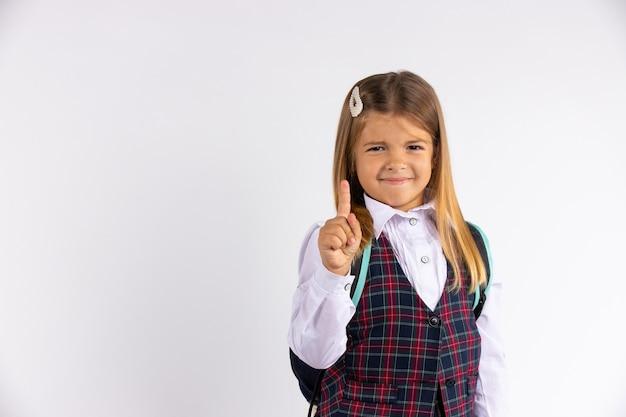 Porträt des kleinen schülerschulmädchens in der uniformkleidungsschule mit lustigem gesicht, das den finger zeigt, lokalisiert auf weißer wand mit leerem raum.