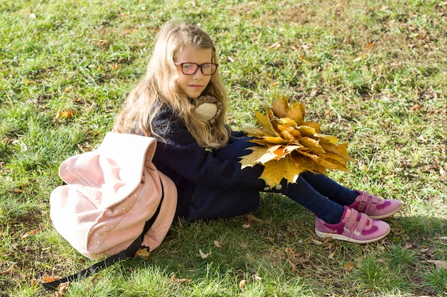 Porträt des kleinen schulmädchens mit gelbem ahorn verlässt schultasche
