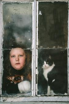 Porträt des kleinen selbstisolierten mädchens mit langweiligem gesicht und ihrem reizenden kätzchen