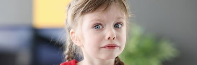 Porträt des kleinen traurigen mädchens im roten kleid psychologische probleme im kinderkonzept