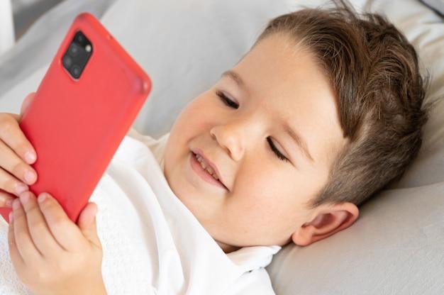 Porträt des kleinkindjungen mit smartphone hautnah. lkid ing auf dem bett und gucke aufs telefon. foto in hoher qualität