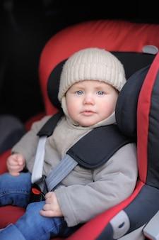 Porträt des kleinkindjungen sitzend im autositz