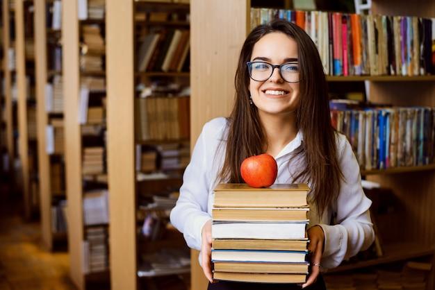 Porträt des klugen schülers mit stapel bücher und roter apfel an der spitze Premium Fotos