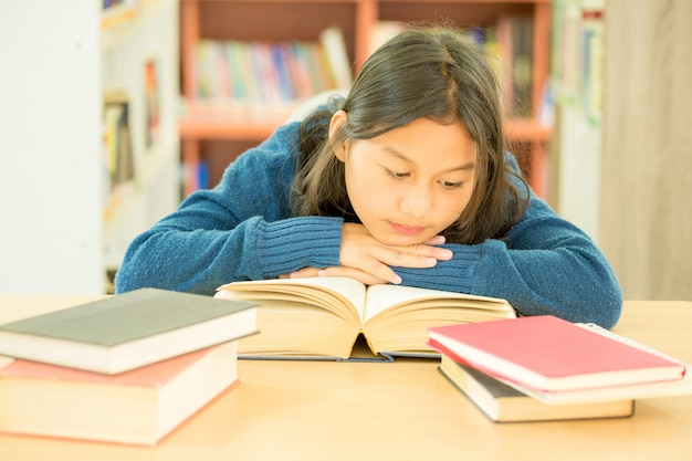 Porträt des klugen studenten mit offenem buch es in der collegebibliothek lesend