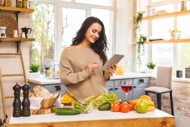 Porträt des kochens der gesunden frau der gesunden nahrung in der küche, die nach einem rezept im internet sucht. tablet-computer verwenden.
